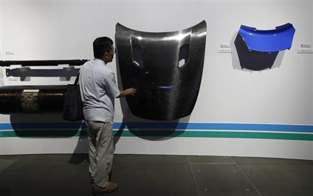 A man looks at components of Toray Industries' prototype electric vehicle TEEWave AR1 during an exhibition showcasing the company's latest technology in Tokyo September 14, 2011. REUTERS/Yuriko Nakao