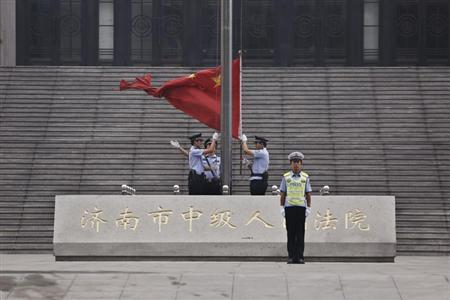 Policemen hoist a Chinese national flag in front of an entrance of the Jinan Intermediate People's Court where the trial of disgraced Chinese politician Bo Xilai will be held, in Jinan, Shandong province September 22, 2013. REUTERS/Aly Song