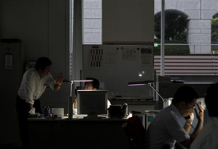 Employees of SMBC Nikko Securities Inc. work using only LED desk lights, during daytime at the company office in Tokyo June 30, 2011, a day before a target to cut electricity use by 15 percent in regions affected by Japan's March 11 earthquake and tsunami takes effect. REUTERS/Toru Hanai