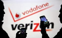 Men are silhouetted against a video screen with Vodafone and Verizon texts as they pose with Blackberry Q10 and Samsung Galaxy S3 in this photo illustration taken in the central Bosnian town of Zenica, September 3, 2013. Picture taken September 3. REUTERS/Dado Ruvic