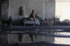 Боец Свободной армии Сирии сидит на кровати в Алеппо 26 сентября 2013 года. Россия и США согласовали проект резолюции Совета безопасности ООН, который потребует от Сирии передать арсеналы химического оружия под международный контроль, но не предполагает военного вторжения в случае, если Дамаск не последует договоренностям. REUTERS/Muzaffar Salman