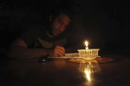 Mostafa Khaled, 20, studies by candlelight for his early morning exams during a power cut in Toukh, El-Kalubia governorate, about 25 km (16 miles) northeast of Cairo May 26, 2013. REUTERS/Amr Abdallah Dalsh