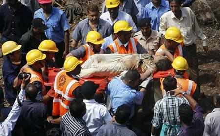 Rescue workers use a stretcher to carry a woman who was rescued from the rubble at the site of a collapsed residential building in Mumbai September 27, 2013. REUTERS/Danish Siddiqui