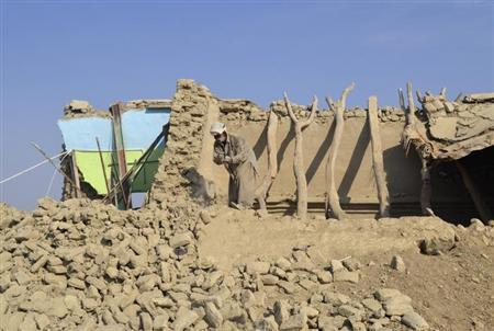 A survivor of an earthquake searches his belongings from the rubble of a mud house after it collapsed following the quake at Dhallbedi Peernder village in Awaran district, southwestern Pakistani province of Baluchistan, September 27, 2013. REUTERS/Naseer Ahmed