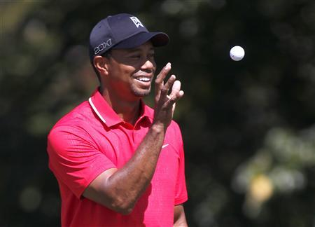 Tiger Woods of the U.S. catches a ball before his putt from his caddie on the second hole in the final round of the Tour Championship golf tournament at East Lake Golf Club in Atlanta, Georgia September 22, 2013. REUTERS/Tami Chappell