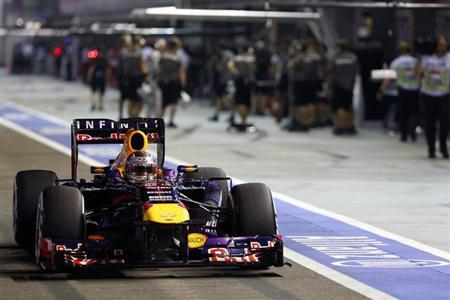 Red Bull Formula One driver Sebastian Vettel of Germany drives in the pit lane during the qualifying session of the Singapore Formula One Grand Prix September 21, 2013. REUTERS/Pablo Sanchez