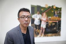 "Chinese artist Liu Xiaodong poses for a portrait in front of his painting titled ""Green Pub"" at the Lisson Gallery in London September 26, 2013. REUTERS/Andrew Winning"