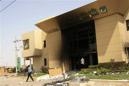 A man passes a burnt bank during protests over fuel subsidy cuts in Khartoum September 26, 2013. REUTERS/ Stringer