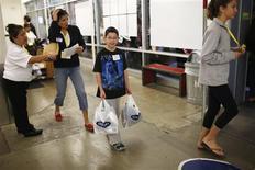 Un niño sonríe tras realizar unas compras en una tienda de la cadena Old Navy en San Jose, EEUU, ago 3 2013. El gasto de los hogares estadounidenses subió en agosto gracias a sólidos aumentos salariales, indicios de que podría estar creciendo el impulso en la economía a pesar de meses de rigurosa austeridad gubernamental. REUTERS/Stephen Lam