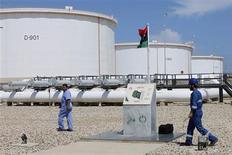 Unos trabajadores junto a unos estanques de crudo en el puerto y refinería de Zawiya, Libia, ago 22 2013. Las exportaciones de petróleo de Libia han subido a más de 580.000 barriles por día tras la reapertura este mes de yacimientos en el oeste del país, aunque las instalaciones de exportación de crudo en el este permanecen bloqueadas por manifestantes, dijo el viernes un ejecutivo de la industria. REUTERS/Ismail Zitouny