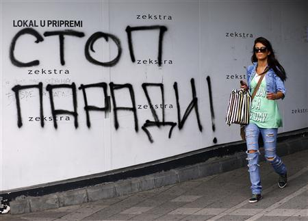 A woman walks past a graffiti reading, ''Stop the parade'' in Belgrade September 26, 2013. REUTERS/Marko Djurica