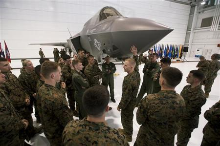 Major Mike Rountree, (C) a marine fighter attack training officer, shows naval flight students a U.S. Marine F-35B Joint Strike Fighter Jet during a roll-out ceremony at Eglin Air Force Base in Florida, February 24, 2012. REUTERS/Michael Spooneybarger