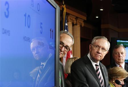 U.S. Senate Majority Leader Harry Reid (D-NV) (3rd R) looks at a screen showing a clock counting down to a government shutdown, at a news conference with fellow Democrats Senator Chuck Schumer (D-NY) (4th R), Senator Barbara Mikulski (D-MD) (2nd R) and Senator Dick Durbin (D-IL) (R) after the Senate voted to pass a spending bill in an attempt to avoid the shutdown, sending the issue back to the House of Representatives, at the U.S. Capitol in Washington September 27, 2013. REUTERS/Jonathan Ernst