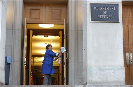 A worker cleans the entryway prior to former U.S. Senator Chuck Hagel's (R-NE) arrival for his first day as Secretary of Defense at the Pentagon in Arlington, Virginia, February 27, 2013. REUTERS/Jonathan Ernst (UNITED STATES - Tags: POLITICS MILITARY) - RTR3ECLL