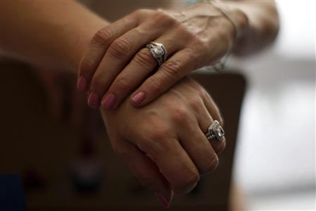 Sallee Taylor, 41, (L) and her wife Andrea Taylor, 41, hold hands after getting married in West Hollywood, California, July 1, 2013. REUTERS/Lucy Nicholson