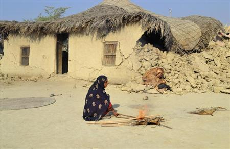 A survivor of an earthquake burns wooden sticks near the rubble of a mud house after it collapsed following the quake at Dhallbedi Peernder village in Awaran district, southwestern Pakistani province of Baluchistan, September 27, 2013. REUTERS/Naseer Ahmed