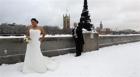 A newly married couple pose for a photograph in the snow opposite the Houses of Parliament, in central London in this December 18, 2010 file photo. REUTERS/Eddie Keogh/Files