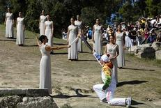 Greek actress Ino Menegaki, playing the role of High Priestess, passes the Olympic flame to Greek skier Yannis Antoniou, the first torchbearer of the torch relay, during a dress rehearsal for the torch lighting ceremony of the Sochi 2014 Winter Olympic Games at the site of ancient Olympia in Greece September 28, 2013. REUTERS/Yannis Behrakis
