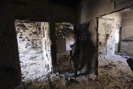 A Free Syrian Army fighter holds a weapon as he stands inside a room in Deir al-Zor September 28, 2013. REUTERS-Khalil Ashawi