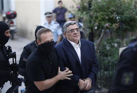 Far-right Golden Dawn party leader Nikos Mihaloliakos (R) is escorted by anti-terrorism police officers as he arrives at a courthouse in Athens September 28, 2013. REUTERS-Giorgos Moutafis