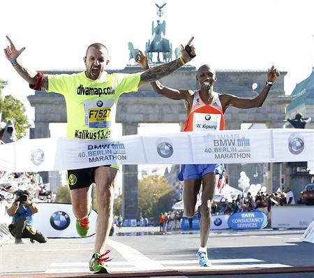 Wilson Kipsang of Kenya crosses the finish line behind a disrupter at the 40th Berlin marathon, September 29, 2013. REUTERS/Tobias Schwarz
