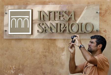 A man takes a picture in front of Intesa Sanpaolo bank in downtown Rome July 23, 2010. REUTERS/Alessandro Bianchi