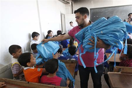 A man distributes bags donated from UNICEF to young students in Raqqa, eastern Syria September 29, 2013. The distribution of around 60,000 bags containing school supplies is part of aid from UNICEF for young students in Raqqa. REUTERS/Nour Fourat (SYRIA - Tags: POLITICS CIVIL UNREST SOCIETY EDUCATION) - RTR3FF2D