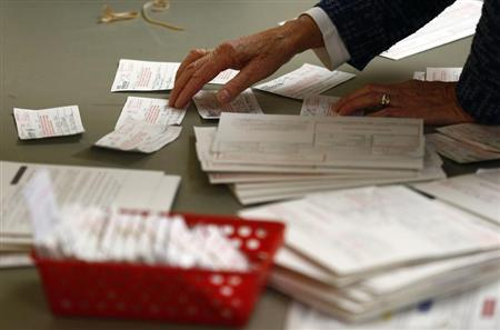 A poll worker looks at voter authorization forms and provisional ballots after the polls closed at the Covenant Presbyterian Church during the U.S. presidential election in Charlotte, North Carolina November 6, 2012. REUTERS/Chris Keane