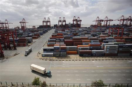 Container trucks drive past the container area at the Yangshan Deep Water Port, part of the newly announced Shanghai Free Trade Zone, south of Shanghai September 26, 2013. REUTERS/Carlos Barria
