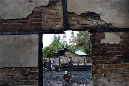 Muslim people clear the area and search for salvageable items, after their houses were burnt in a riot at Htan Kone village, in Myanmar's northern Sagaing region August 26, 2013. REUTERS/Soe Zeya Tun