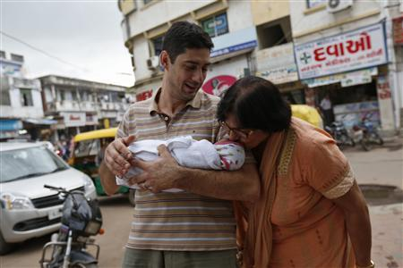 Daniele Fabbricatore, 39, holds his week-old daughter Gabriella, who is kissed by her maternal grandmother Vanita Patel, outside the Akanksha IVF centre in Anand town, about 70 km (44 miles) south of the western Indian city of Ahmedabad August 26, 2013. REUTERS/Mansi Thapliyal