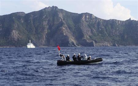 A Japan Coast Guard boat (front) and vessel sail as Uotsuri island, one of the disputed islands, called Senkaku in Japan and Diaoyu in China, is pictured in the background, in the East China Sea August 18, 2013. REUTERS/Ruairidh Villar/Files