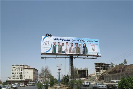 Workers put up a billboard urging citizens to cooperate with security authorities in Sanaa September 30, 2013. At least three Yemeni soldiers were killed and six wounded on Monday when a group of suspected al Qaeda militants disguised as security personnel seized an army base in the southeastern city of al-Mukalla, a military official said. REUTERS/Khaled Abdullah