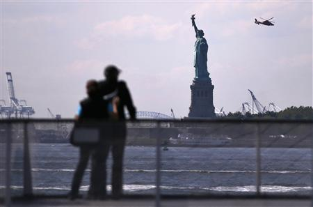 Tourists pause to view the Statue of Liberty from a Liberty Island ferry boat at Battery Park in New York, September 30, 2013. REUTERS/Mike Segar