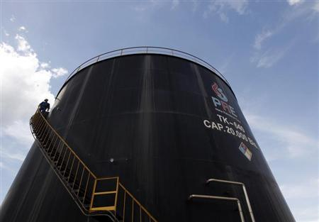 An employee of the Canadian Pacific Rubiales Petroleum Company ascends an oil storage tank in Campo Rubiales field in Meta, eastern Colombia April 21, 2010. REUTERS/Jose Miguel Gomez