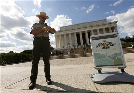 U.S. National Park Ranger Mark Ragan checks his watch while on duty in front of the Lincoln Memorial in Washington September 30, 2013. REUTERS/Kevin Lamarque