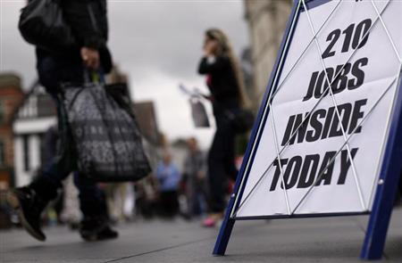 Shoppers walk past a newspaper advertising board promoting its job supplement in Leicester, central England, September 14, 2011. REUTERS/Darren Staples