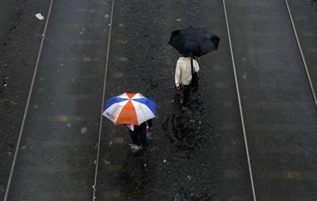 People walk over waterlogged railway tracks after getting off a stalled train during heavy monsoon rains in Mumbai July 23, 2013. REUTERS/Vivek Prakash/Files