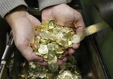 Работник монетного двора в Санкт-Петербурге держит только что отчеканенные десятирублевые монеты 9 февраля 2010 года. Рубль незначительно подорожал к доллару и бивалютной корзине, отразив умеренную слабость американской валюты в условиях сокращения финансирования госструктур США. REUTERS/Alexander Demianchuk
