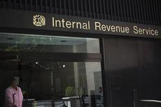 Женщина выходит из здания Налогового управления США в Нью-Йорке 13 мая 2013 года. Администрация США впервые за 17 лет оказалась вынуждена частично приостановить работу, что грозит стране далеко идущими последствиями. REUTERS/Shannon Stapleton