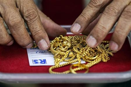 A pawn shop worker sorts through gold jewellery at Easy Money Pawn shop in Bangkok, August 27, 2013. REUTERS/Athit Perawongmetha/Files