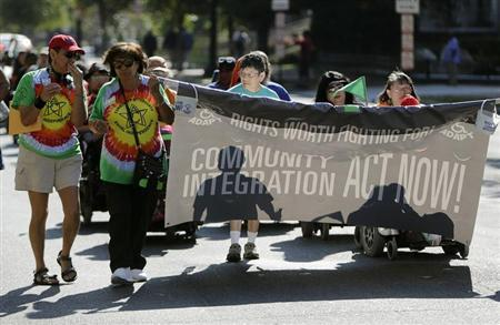 Members of ADAPT, a grassroots disability rights group that supports Obamacare, march in Washington during the U.S. government shutdown October 1, 2013. REUTERS/Gary Cameron
