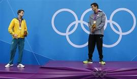 Gold medallist Nathan Adrian of the U.S. (R) and silver medallist James Magnussen of Australia stand on the podium with their medals during the men's 100m freestyle victory ceremony at the London 2012 Olympic Games at the Aquatics Centre August 1, 2012. REUTERS/David Gray