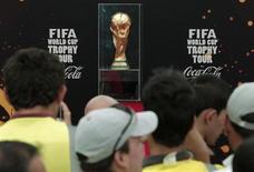 Pessoas observam troféu da Copa Mundial da Fifa no aeroporto de Juan Santamria, na Costa Rica. O chefe da área de investigação da Fifa está aprofundando a análise dos polêmicos procedimentos de votação que escolherem as sedes da Copa do Mundo de 2018 e 2022. 27/09/2013 REUTERS/Juan Carlos Ulate