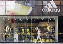 Mulher passa em frente a lonja da Adidas, em Pequim. A Reebok está se voltando para acordos de patrocínio com grupos proeminentes de fitness para tentar ressuscitar uma marca venerável que tem desaparecido desde que se tornou parte do grupo alemão de material esportivo Adidas, oito anos atrás. 25/03/2013 REUTERS/Kim Kyung-Hoon