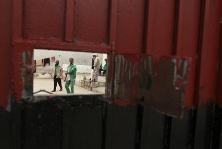 Suspected loyalists of Muammar Gaddafi stand inside a jail in Tripoli November 17, 2011. REUTERS/Mohammed Salem