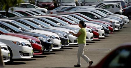A woman walks by vehicles for sale at a Toyota dealership in Pasadena, California October 10, 2012. REUTERS/Mario Anzuoni