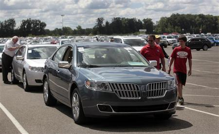 Auto dealership owners take a look at vehicles being auctioned off during an auto auction at Manheim Detroit Auto Auction in Carleton, Michigan August 14, 2013. REUTERS/Rebecca Cook