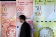 A man walks past big samples of Venezuelan bank notes at the Central Bank headquarters in Caracas August 22, 2013. REUTERS/Carlos Garcia Rawlins