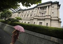 A pedestrian holding an umbrella walks past the Bank of Japan (BOJ) headquarters in Tokyo, in this August 8, 2013 file picture. REUTERS/Yuya Shino/Files